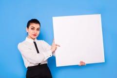Affärskvinna i formella kläder med den vita panelen på blå backgroun royaltyfri foto