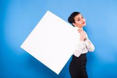 Affärskvinna i formella kläder med den vita panelen på blå backgroun royaltyfri bild