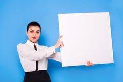 Affärskvinna i formella kläder med den vita panelen på blå backgroun arkivfoton