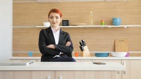 Affärskvinna i formellt dräkthem på köket som ler till kameran arkivfilmer