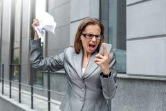 Affärskvinna i glasögon som står på stadsgatan som ropar på det ilskna skrynklande avtalet för smartphone royaltyfri bild