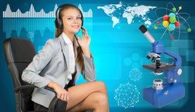 Affärskvinna i hörlurar med mikrofon, atommodell och Arkivfoton