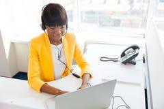 Affärskvinna i hörlurar med mikrofon genom att använda bärbar datordatoren Arkivbilder