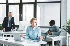 affärskvinna i hörlurar med mikrofon genom att använda bärbara datorn och se kameran medan manliga kollegor som bakom arbetar royaltyfri fotografi