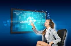 Affärskvinna i hörlurar med mikrofon genom att använda pekskärmen Royaltyfri Fotografi