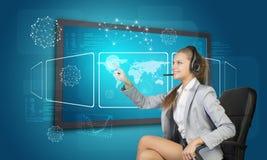 Affärskvinna i hörlurar med mikrofon genom att använda pekskärmen Arkivbilder