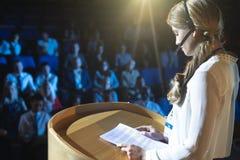 Affärskvinna i hörlurar med mikrofon som ger presentation i salongen royaltyfri foto