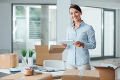 Affärskvinna i hennes nya kontor genom att använda en minnestavla Arkivfoton