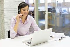 Affärskvinna i kontoret på telefonen med hörlurar med mikrofon, Skype royaltyfria bilder