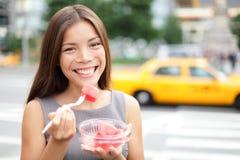 Affärskvinna i New York som äter vattenmelonmellanmålet Arkivfoto