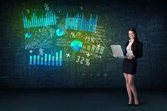 Affärskvinna i regeringsställning med bärbara datorn i hand och tekniskt avancerade grafdiagram arkivfoton