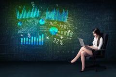 Affärskvinna i regeringsställning med bärbara datorn i hand och tekniskt avancerad graf royaltyfria foton