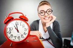 Affärskvinna i regeringsställning med den stora röda klockan Royaltyfri Foto