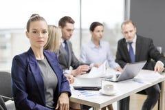 Affärskvinna i regeringsställning med laget på baksidan Royaltyfri Fotografi