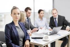 Affärskvinna i regeringsställning med laget på baksidan Fotografering för Bildbyråer