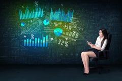 Affärskvinna i regeringsställning med minnestavlan i hand och tekniskt avancerad graf arkivbild