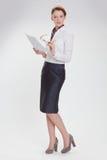 Affärskvinna i regeringsställning med papper, htb och exponeringsglas Arkivfoto