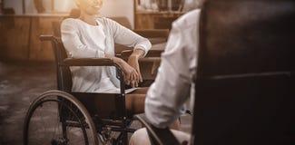 Affärskvinna i rullstol som i regeringsställning talar med kollegan arkivbilder