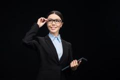 Affärskvinna i svart dräkt genom att använda den digitala minnestavlan som isoleras på svart Arkivfoto