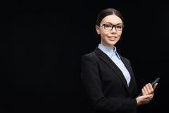 Affärskvinna i svart dräkt genom att använda den digitala minnestavlan som isoleras på svart Royaltyfri Foto