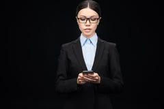 Affärskvinna i svart dräkt genom att använda smartphonen som isoleras på svart Arkivbilder