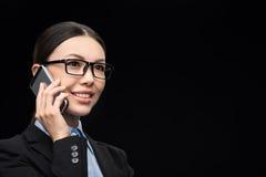 Affärskvinna i svart dräkt genom att använda smartphonen som isoleras på svart Arkivfoto