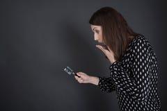 Affärskvinna i svart som söker uttryck och villkor med magn arkivbild