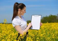 Affärskvinna i utomhus- blick för blommafält på skrivplattan Ung flicka i gult rapsfröfält Härligt vårlandskap som är ljust arkivfoto