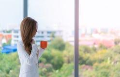 Affärskvinna i vit som rymmer en röd kaffekopp vid fönstren fotografering för bildbyråer
