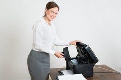 Affärskvinna With Laser Cartridge och skrivare At Desk Arkivbild