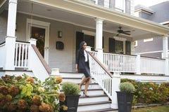 Affärskvinna Leaving Suburban House för att pendlingssträckan ska arbeta royaltyfria bilder