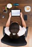 Affärskvinna Looking At Calendar på den Digital minnestavlan Royaltyfri Foto