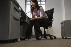 Affärskvinna Looking In Drawer, medan tala på telefonen i regeringsställning royaltyfri fotografi