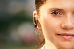 Affärskvinna med att le för telefonbluetoothhörlurar med mikrofon Arkivbilder