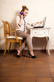 Affärskvinna med bärbara datorn för rörande skärm för telefon Royaltyfri Bild