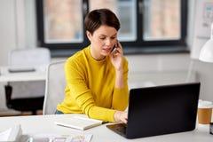 Affärskvinna med bärbara datorn som kallar på smartphonen arkivbilder