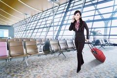 Affärskvinna med bagage och telefonen på flygplatsen Arkivbild