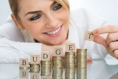 Affärskvinna med budget- kvarter på staplade mynt Arkivfoto