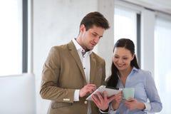 Affärskvinna med den manliga kollegan som i regeringsställning använder minnestavladatoren Arkivbild