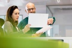 Affärskvinna med den manliga kollegan som i regeringsställning diskuterar över dokument arkivbild