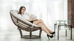 Affärskvinna med dokument som sitter rundan en bekväm stol royaltyfri bild