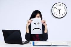 Affärskvinna med en ledsen emoticon arkivfoton
