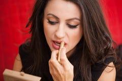 Affärskvinna med en sminkspegel arkivfoto