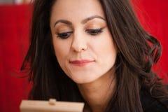 Affärskvinna med en sminkspegel royaltyfri fotografi