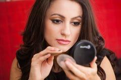 Affärskvinna med en sminkspegel arkivbild