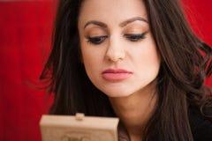 Affärskvinna med en sminkspegel arkivfoton