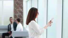 Affärskvinna med ett digitalt minnestavlaanseende nära kontorsfönstret fotografering för bildbyråer