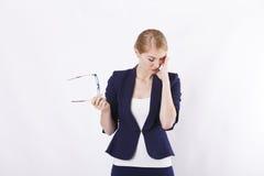 Affärskvinna med exponeringsglas i omslag med tröttade exponeringsglas i spänning och Arkivbild