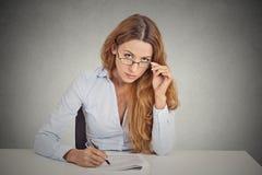 Affärskvinna med exponeringsglas som sitter på skrivbordet som ser skeptically dig som undersöker mycket noggrant Royaltyfri Fotografi