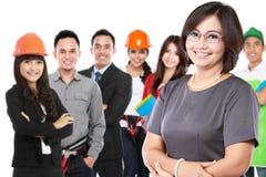 Affärskvinna med gruppen av den yrkesmässiga arbetaren på backgrounen arkivbild